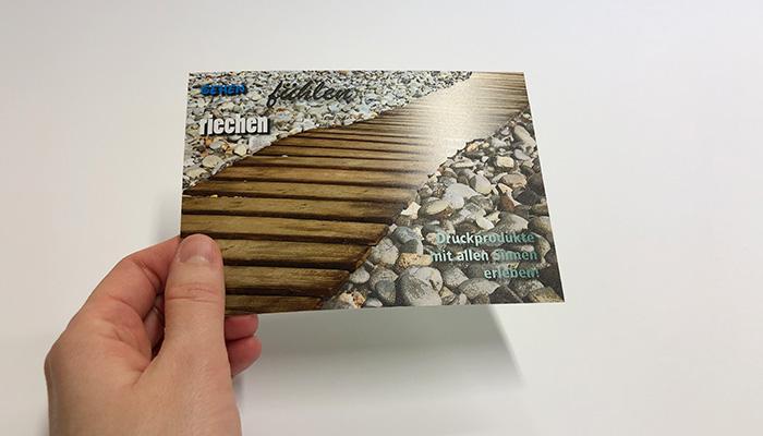 Druckveredelung im UV-Offsetdruck: Haptisch und olfaktorisch interessante Postkarte mit Duftlack (Holz) und Relieflack (Steine)