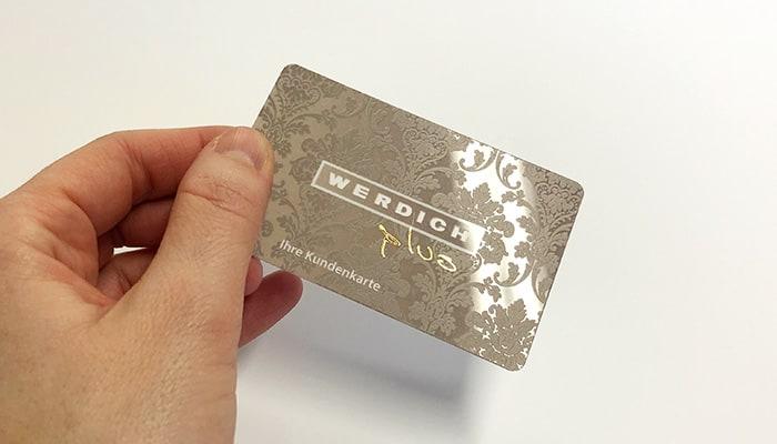 Druckveredelung im Siebdruck: Hochwertige Kundenkarte mit floralem Hintergrunddruck veredelt mit Relieflack sowie Goldfolienprägung